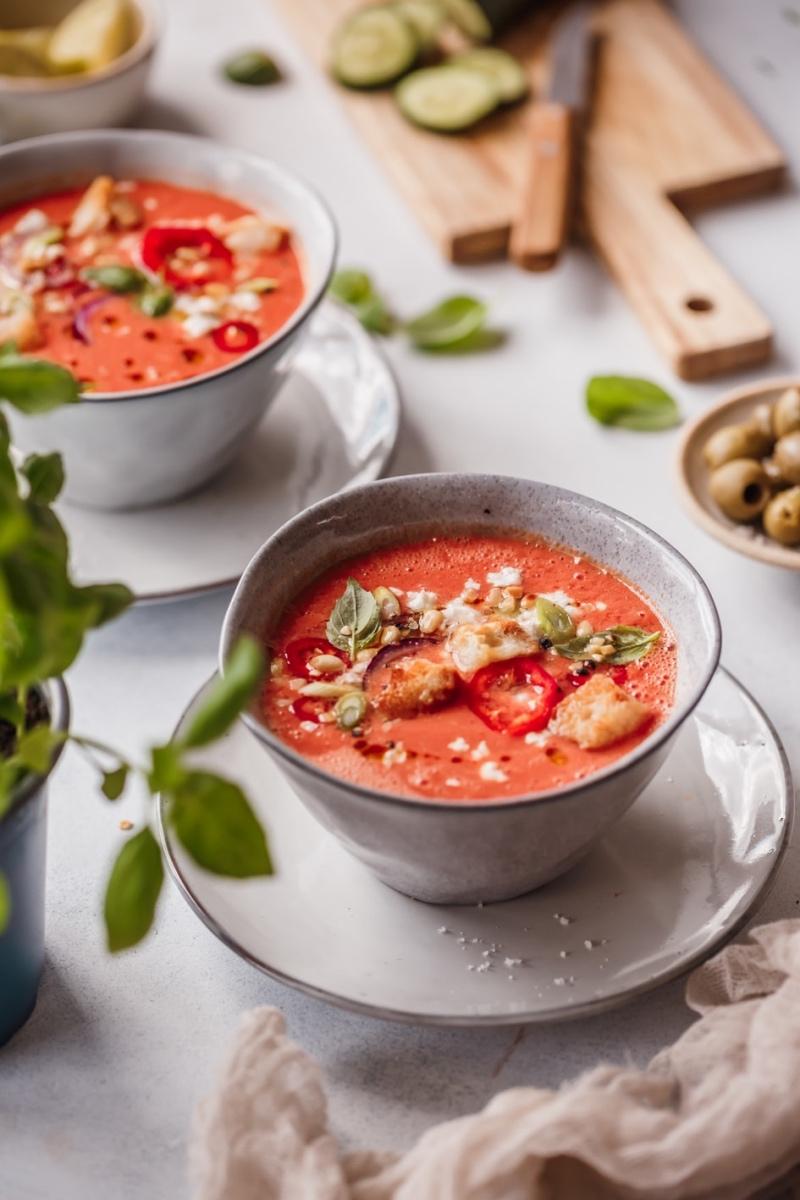 Zwei Schüsseln Wassermelonen-Gazpacho mit Toppings und Zutaten