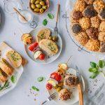 Glutenfreie Grillbrote mit Gemüsespießen und Oliven auf gedecktem Tisch