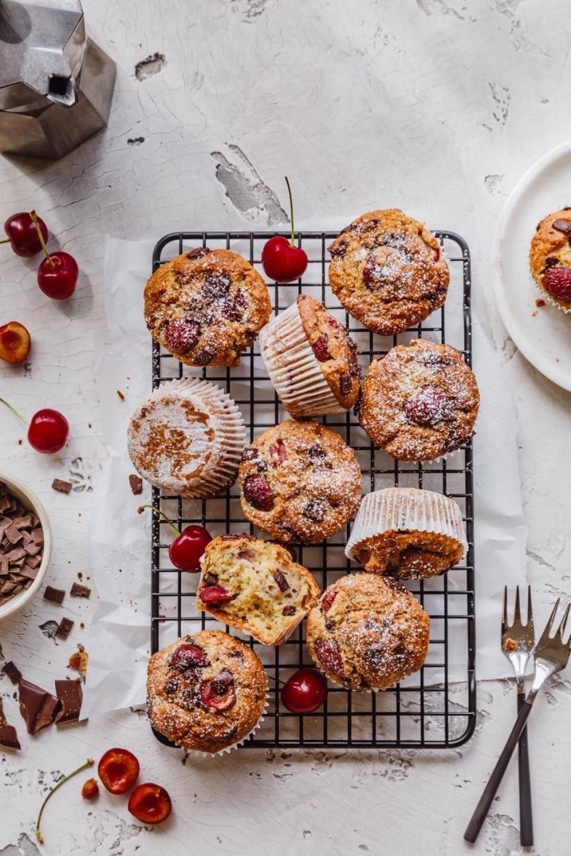 Mehrere Kirschmuffins auf Kuchenrost und Zutaten