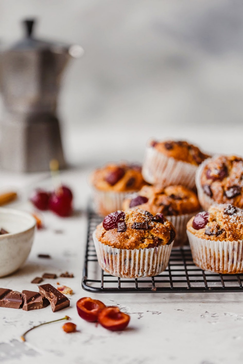 Muffins mit Kirschen übereinander auf Kuchenrost und Zutaten