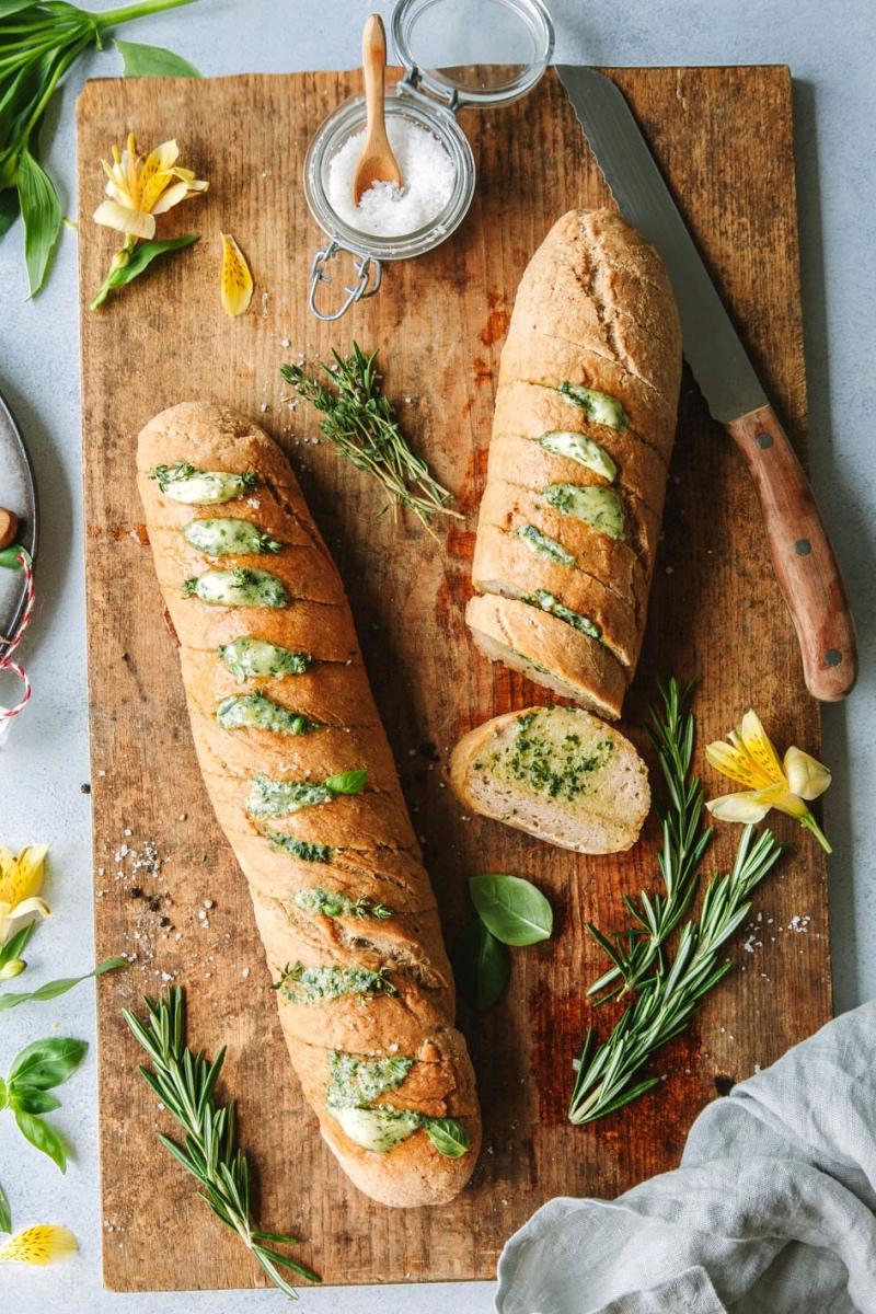 Zwei glutenfreie Kräuterbaguettes auf Holzbrett mit Kräutern und Salz