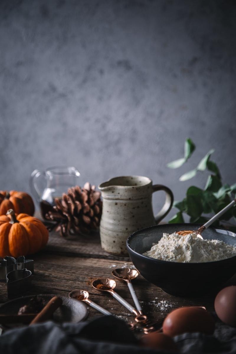 Mehl, Kürbis und Backutensilien auf Holztisch