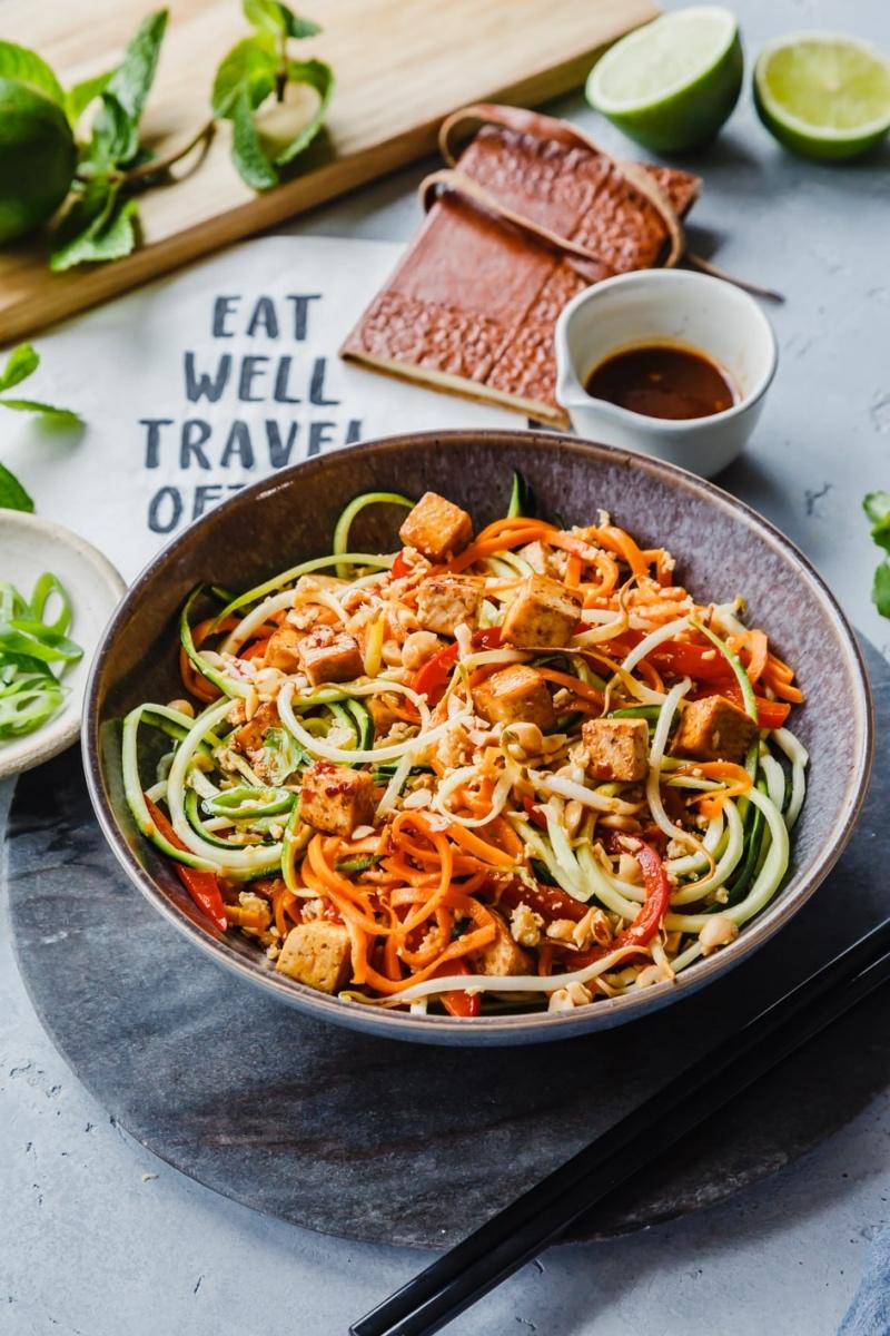 Pad Thai mit Tofu und Gemüsenudeln in Schüssel sowie Sauce