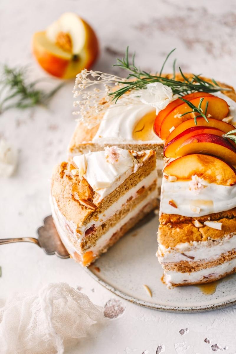 Angeschnittene Pfirsich-Quark-Torte auf Tortenplatte mit Tortenschaufel