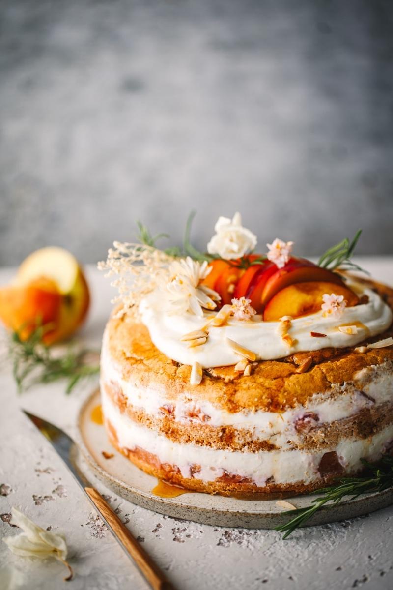 Dekorierte Pfirsich-Quark-Torte auf Tortenplatte mit Messer
