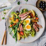 Teller Salat Nicoise mit Besteck und Zutaten