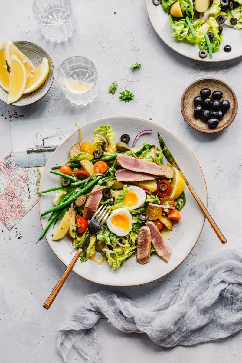 Salat Nicoise mit Teller und Zutaten auf hellem Tisch