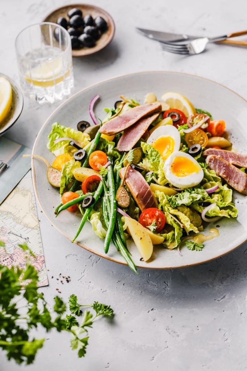 Salat Nicoise mit Petersilie, Oliven und Zitrone auf Tisch