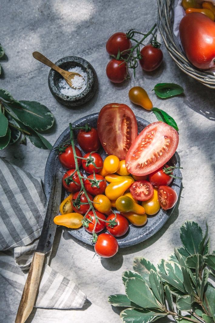 Verschiedene Tomaten auf Teller und Korb