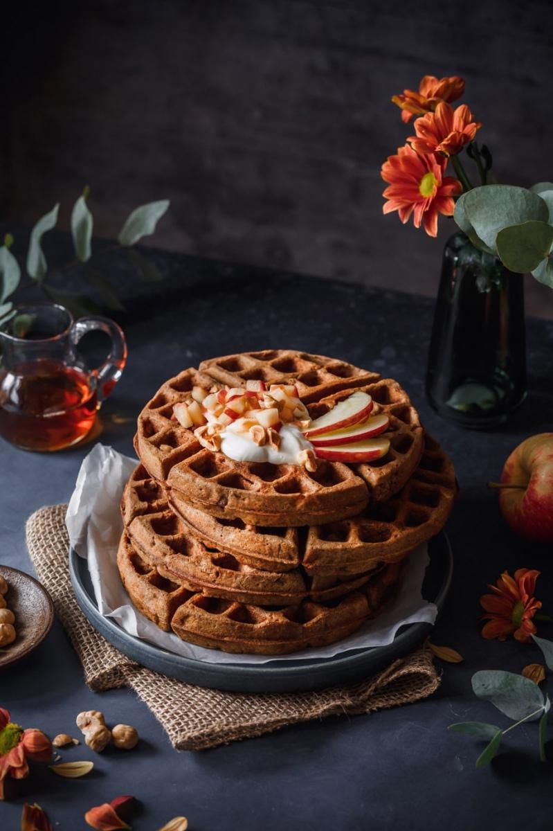 Apfelwaffeln übereinandergestapelt auf herbstlich dekoriertem Tisch